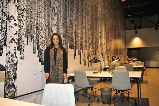 Amity Coworking operations manager Gabrielle Guthrie stands before the eye-catching mural in the recently-opened Northville business.