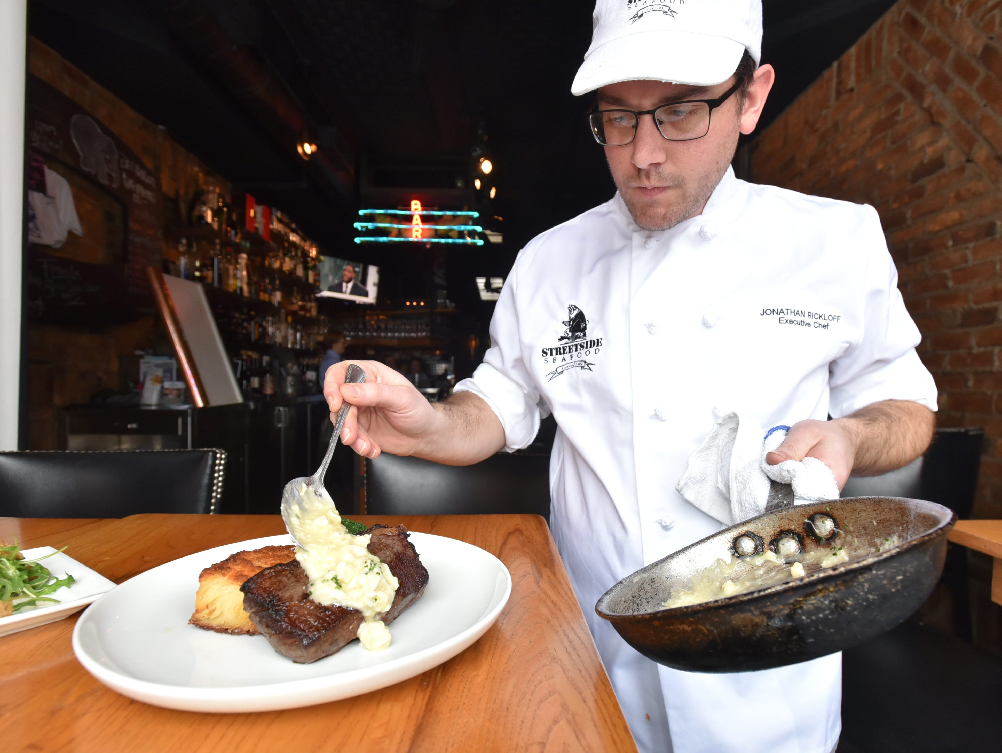 Jonathan Rickloff, executive chef at Birmingham's Streetside Seafood, spoons some creamy anna potatoes on a Prime New York strip steak Oscar at the Pierce Street eatery.