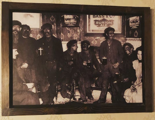 The photo of men covered in soot, drinking at a pub, on the wall in a downtown Phoenix restaurant.
