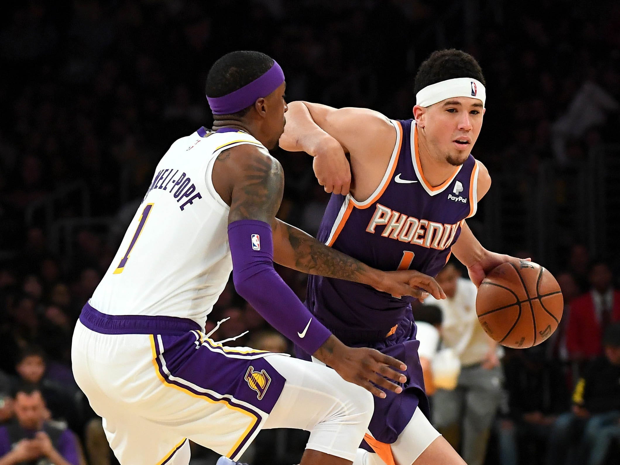 Jan 27, 2019: Los Angeles Lakers guard Kentavious Caldwell-Pope (1) guards Phoenix Suns guard Devin Booker (1) as he drives to the basket in the first half of the game at Staples Center.