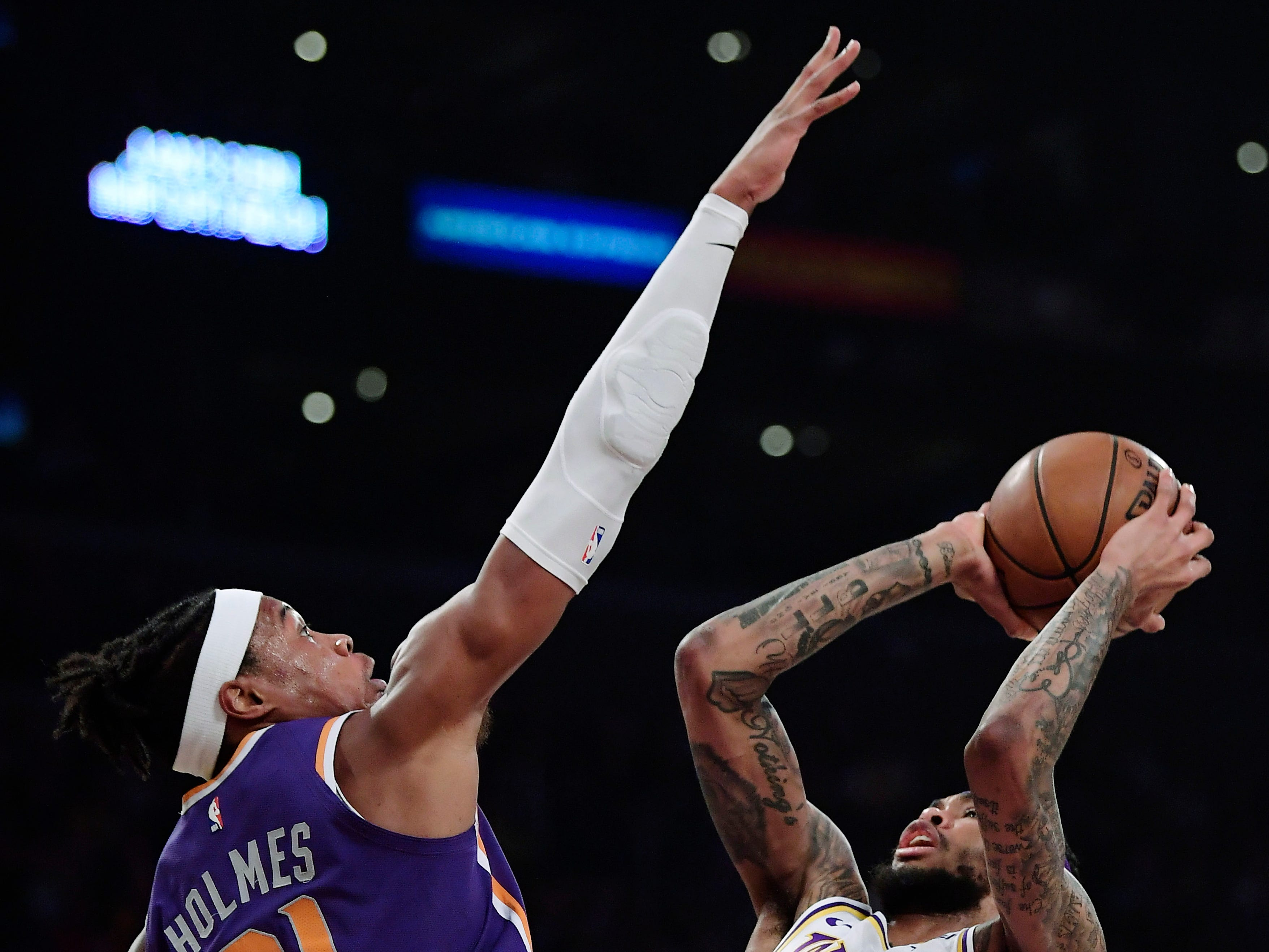 Los Angeles Lakers forward Brandon Ingram, right, shoots as Phoenix Suns forward Richaun Holmes defends during the first half on Sunday, Jan. 27, 2019, in Los Angeles. (AP Photo/Mark J. Terrill)