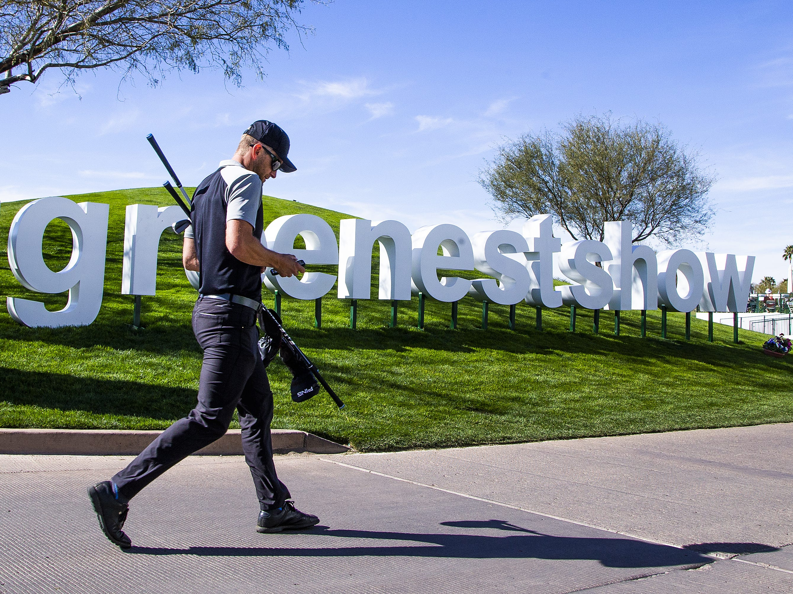A golfer walks by the #greenestshow sign during the Kadima.Ventures Pro-Am at the Waste Management Phoenix Open at the TPC Scottsdale, Monday, January 28, 2019.