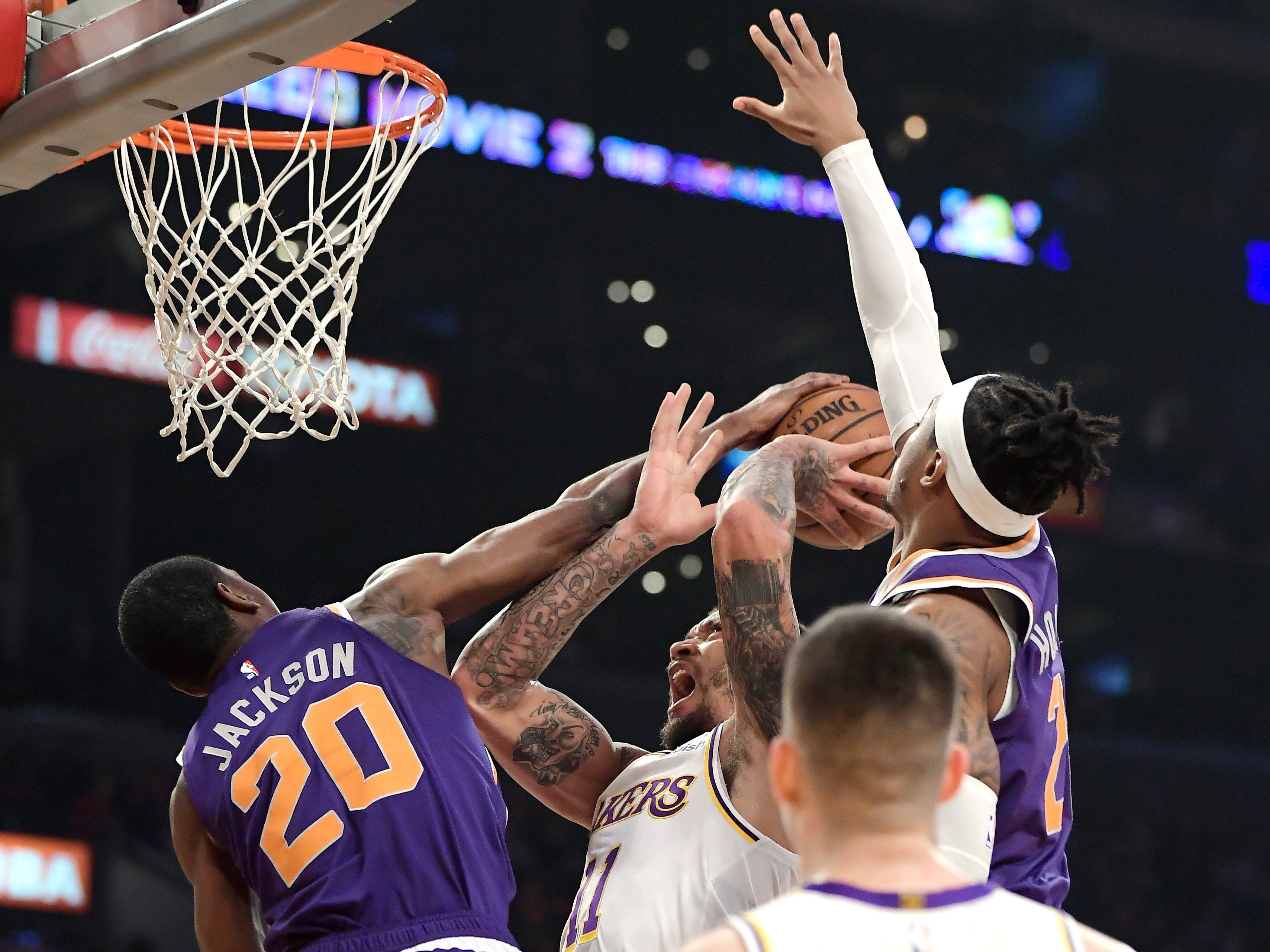 Los Angeles Lakers forward Michael Beasley, second from left, shoots as Phoenix Suns forward Josh Jackson, left, and forward Richaun Holmes, right, defend during the first half on Sunday, Jan. 27, 2019, in Los Angeles. (AP Photo/Mark J. Terrill)