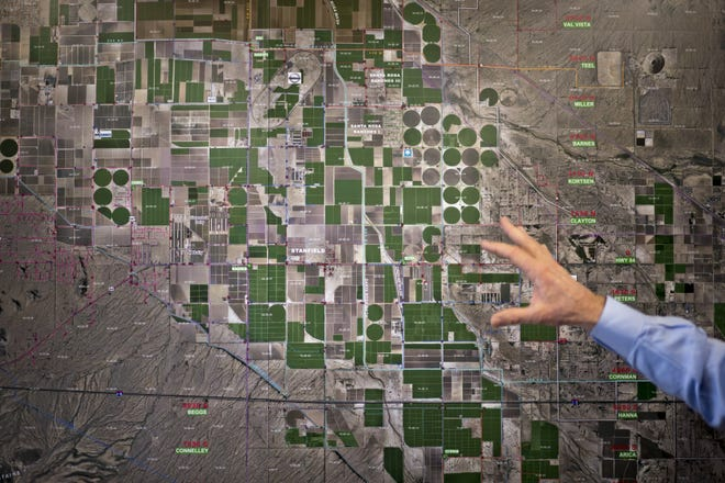Farmer Dan Thelander motions to an aerial photo of farmland at the office of the Maricopa-Stanfield Irrigation District in Pinal County.