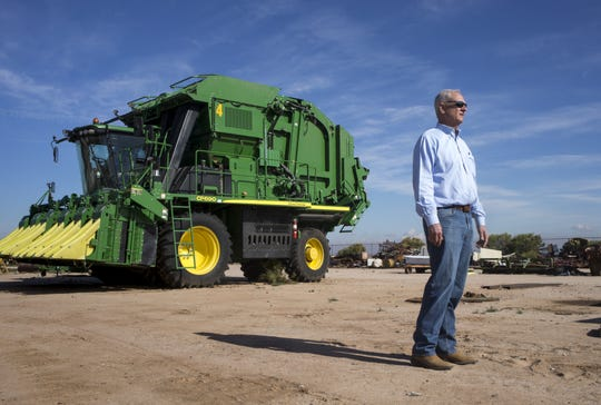 Dan Thelander stands next to his cotton picker at his farm in Pinal County.