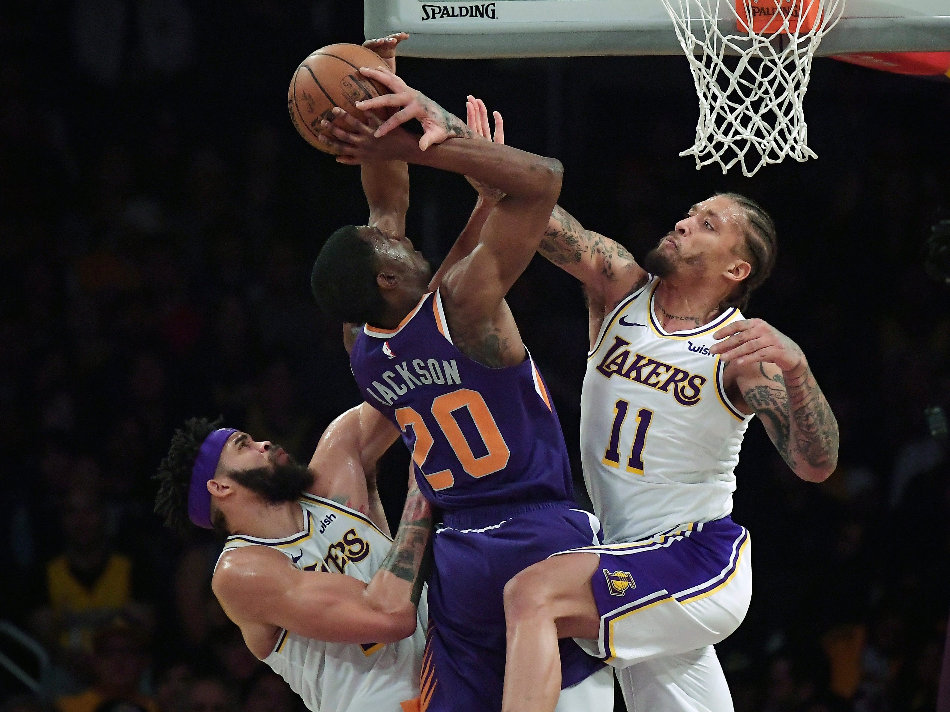 Phoenix Suns forward Josh Jackson, center, shoots as Los Angeles Lakers center JaVale McGee, left, and forward Michael Beasley defend during the first half on Sunday, Jan. 27, 2019, in Los Angeles. (AP Photo/Mark J. Terrill)