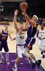 Phoenix Suns guard Devin Booker, second from right, shoots as Los Angeles Lakers center Ivica Zubac, second from left, defends during the first half on Sunday, Jan. 27, 2019, in Los Angeles. (AP Photo/Mark J. Terrill)