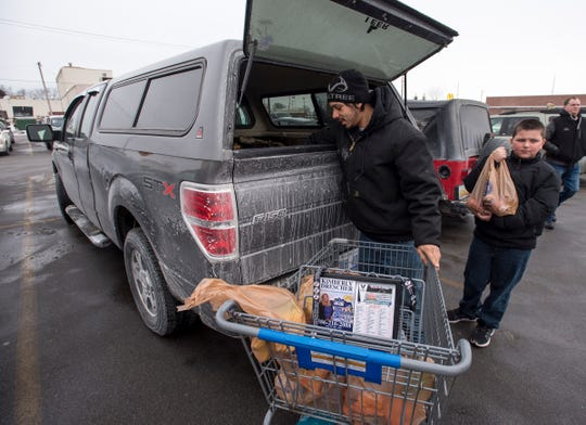 Jamie Garza and his son Loghan, 9, load groceries into the back of his pickup Monday, Jan. 28, 2019 at Kroger in Port Huron. Garza and his son were stocking up on groceries before an expected heavy snowfall moved into the area.