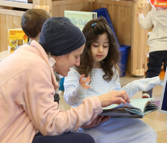 Jenn Birk-Goldschmidt reads to her daughter Amelie during preschooler learning center story time and guided play at Adriance Memorial Library in the City of Poughkeepsie on January 28, 2019.