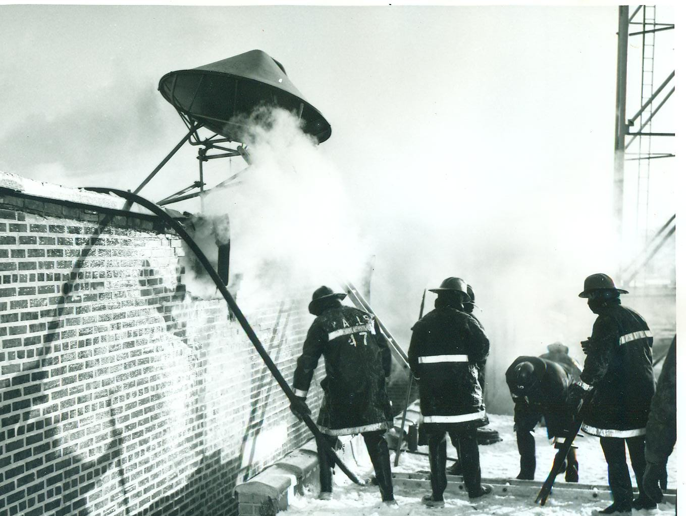 Firefighters jack-hammered a hole in the roof and doused flames using lowered fire hoses to battle a fire at Richmond's General Telephone headquarter in 1965.