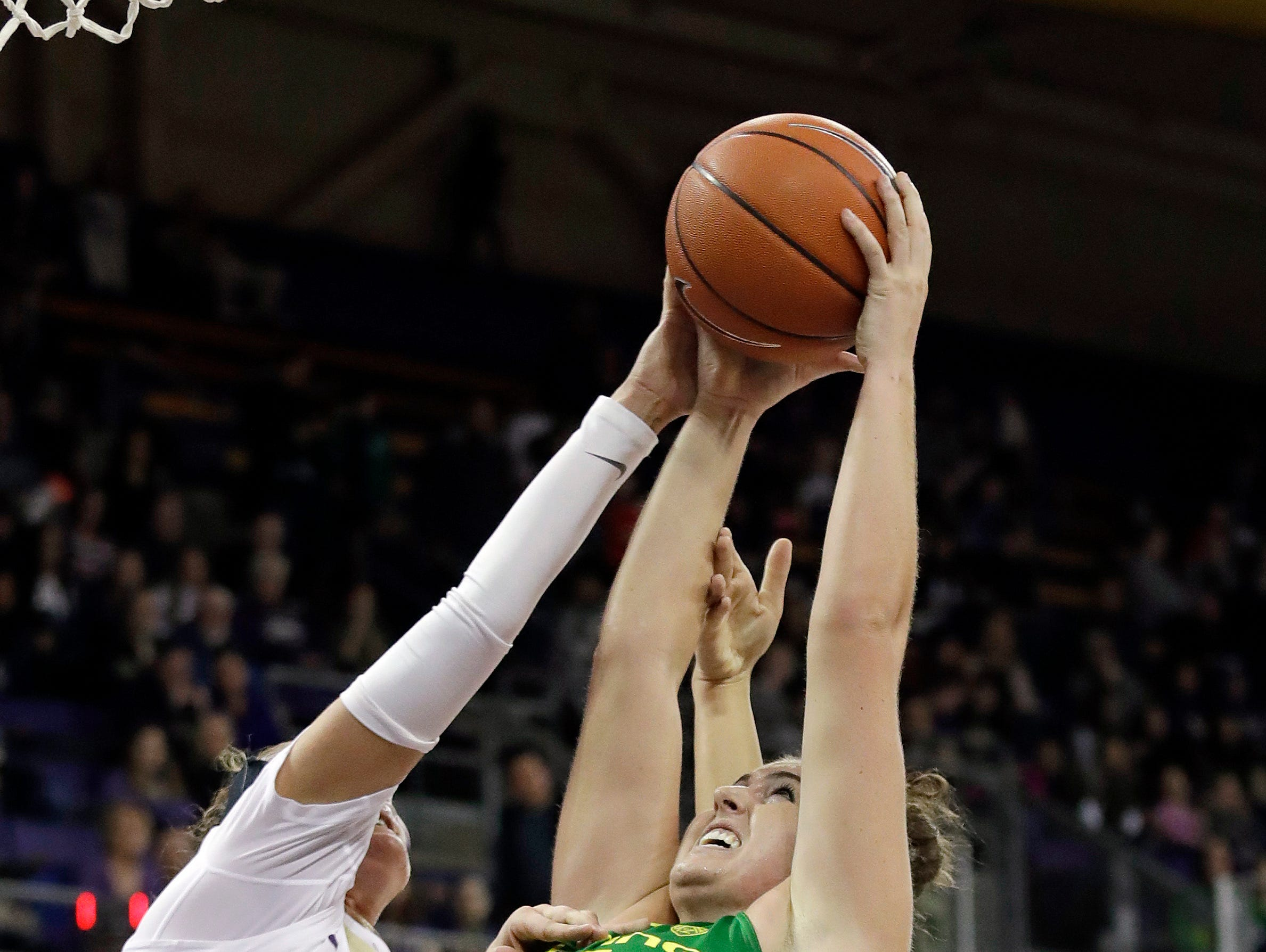 Oregon's Erin Boley (21) grabs a rebound in front of Washington's Missy Peterson (44) and Montana Hagstrom in the second half of an NCAA college basketball game Sunday, Jan. 27, 2019, in Seattle.
