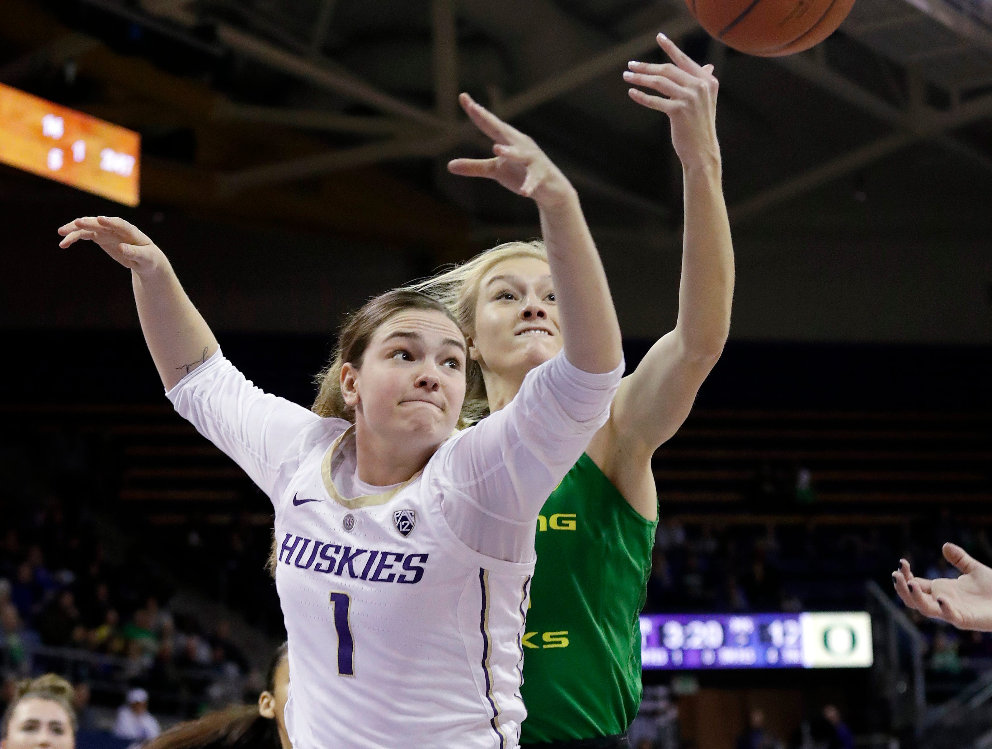 Washington's Hannah Johnson (1) and Oregon's Lydia Giomi reach for a rebound in the first half of an NCAA college basketball game Sunday, Jan. 27, 2019, in Seattle.