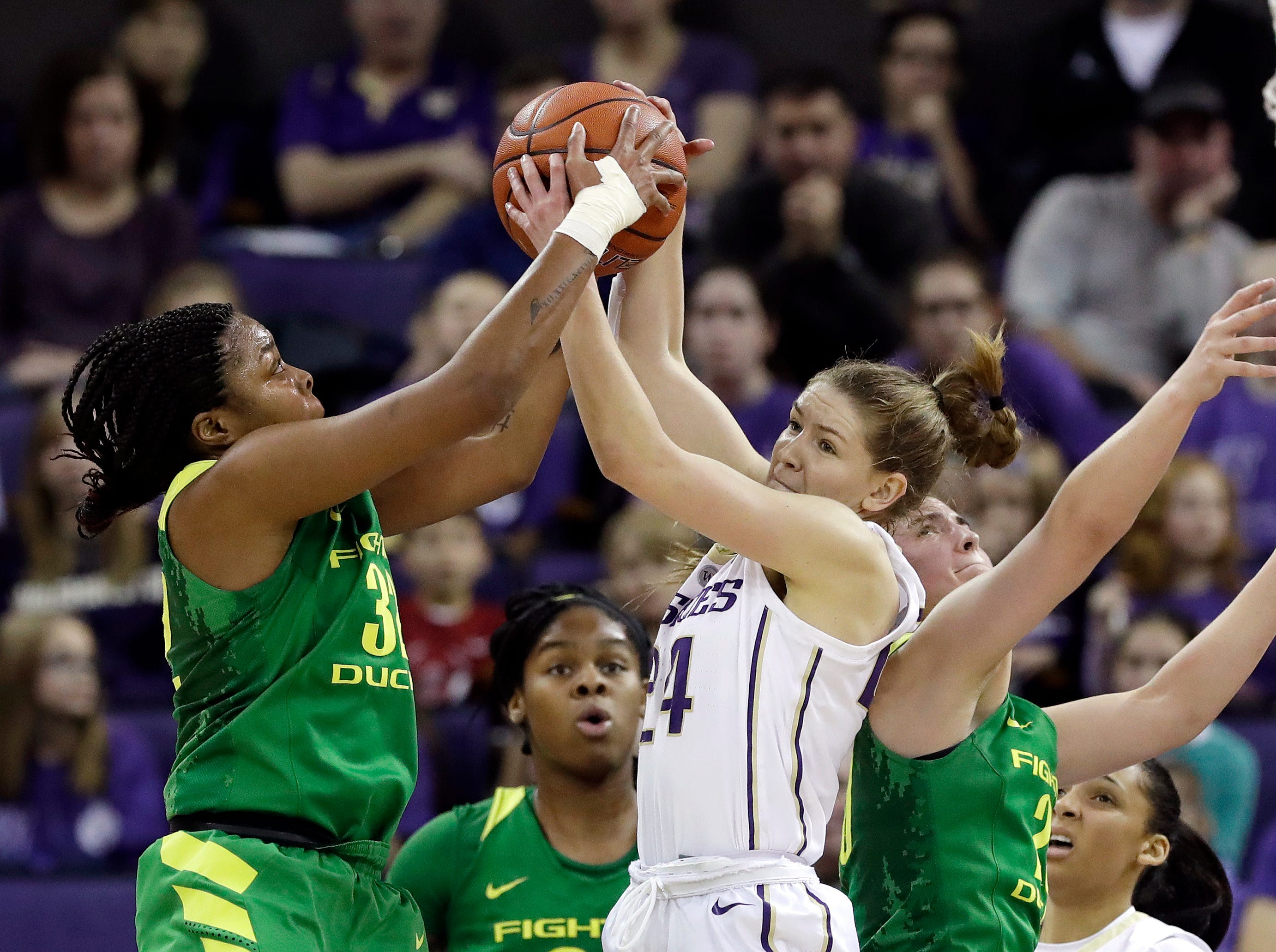 Washington's Jenna Moser (24) reaches for a rebound between Oregon's Oti Gildon, left, and Sabrina Ionescu in the second half of an NCAA college basketball game Sunday, Jan. 27, 2019, in Seattle. Oregon won 76-57.