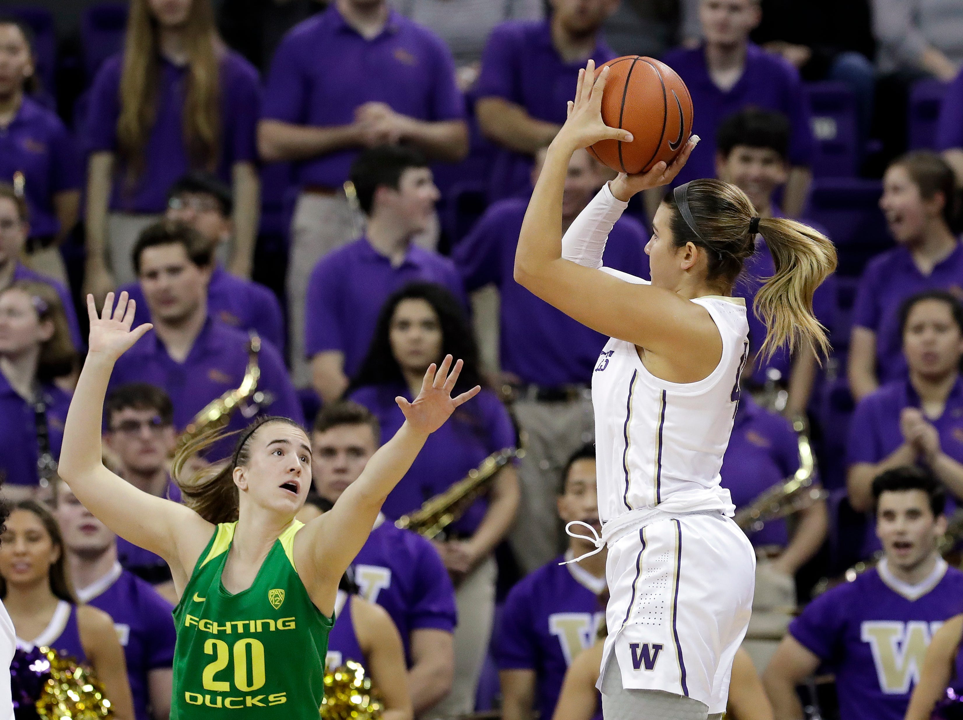 Washington's Amber Melgoza, right, takes a shot over Oregon's Sabrina Ionescu to score in the first half of an NCAA college basketball game Sunday, Jan. 27, 2019, in Seattle. The shot put Melgoza over 1,000 points in her career.