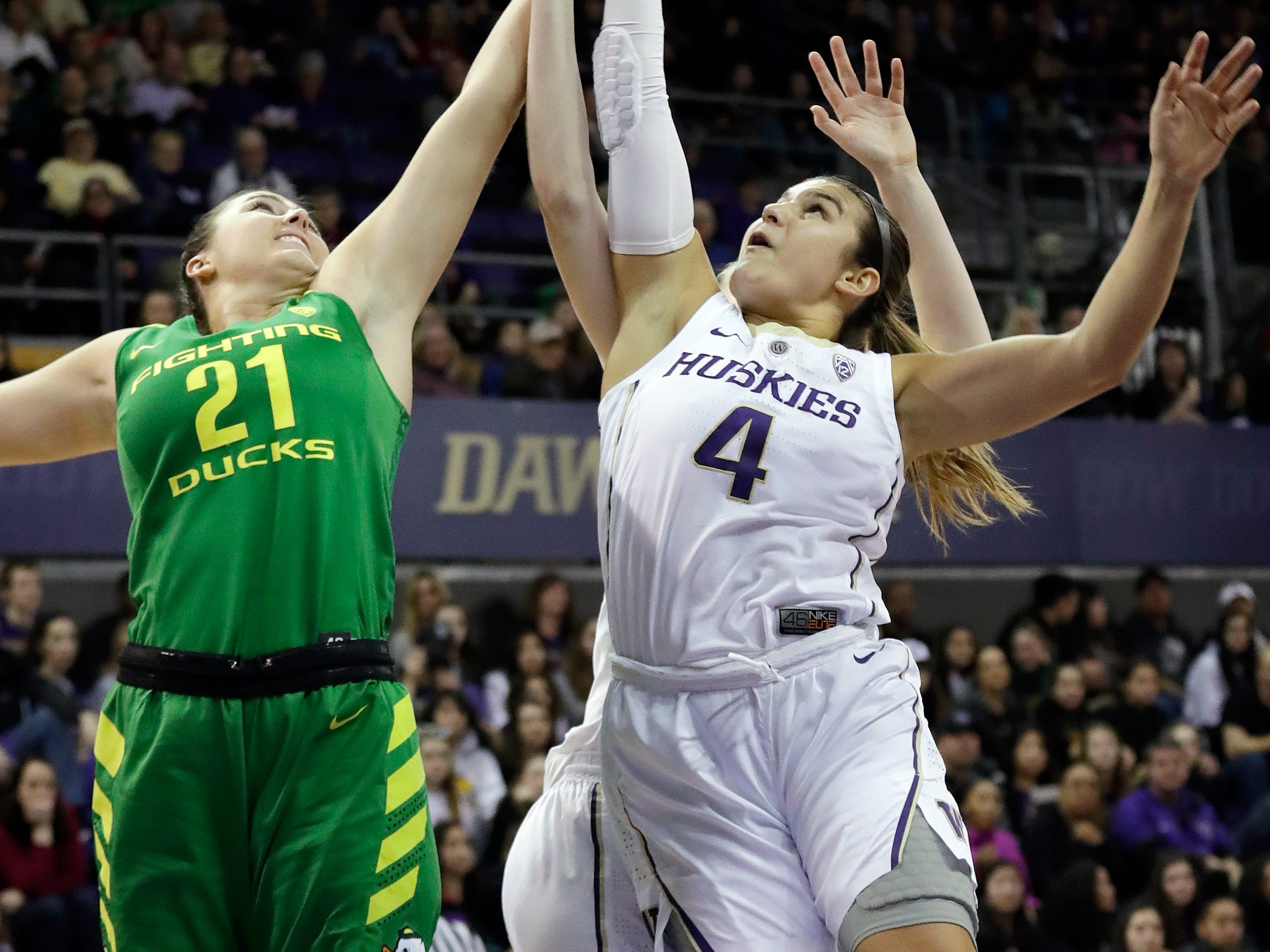 Oregon's Morgan Yaeger (21) and Washington's Amber Melgoza (4) reach for a rebound in the first half of an NCAA college basketball game Sunday, Jan. 27, 2019, in Seattle.