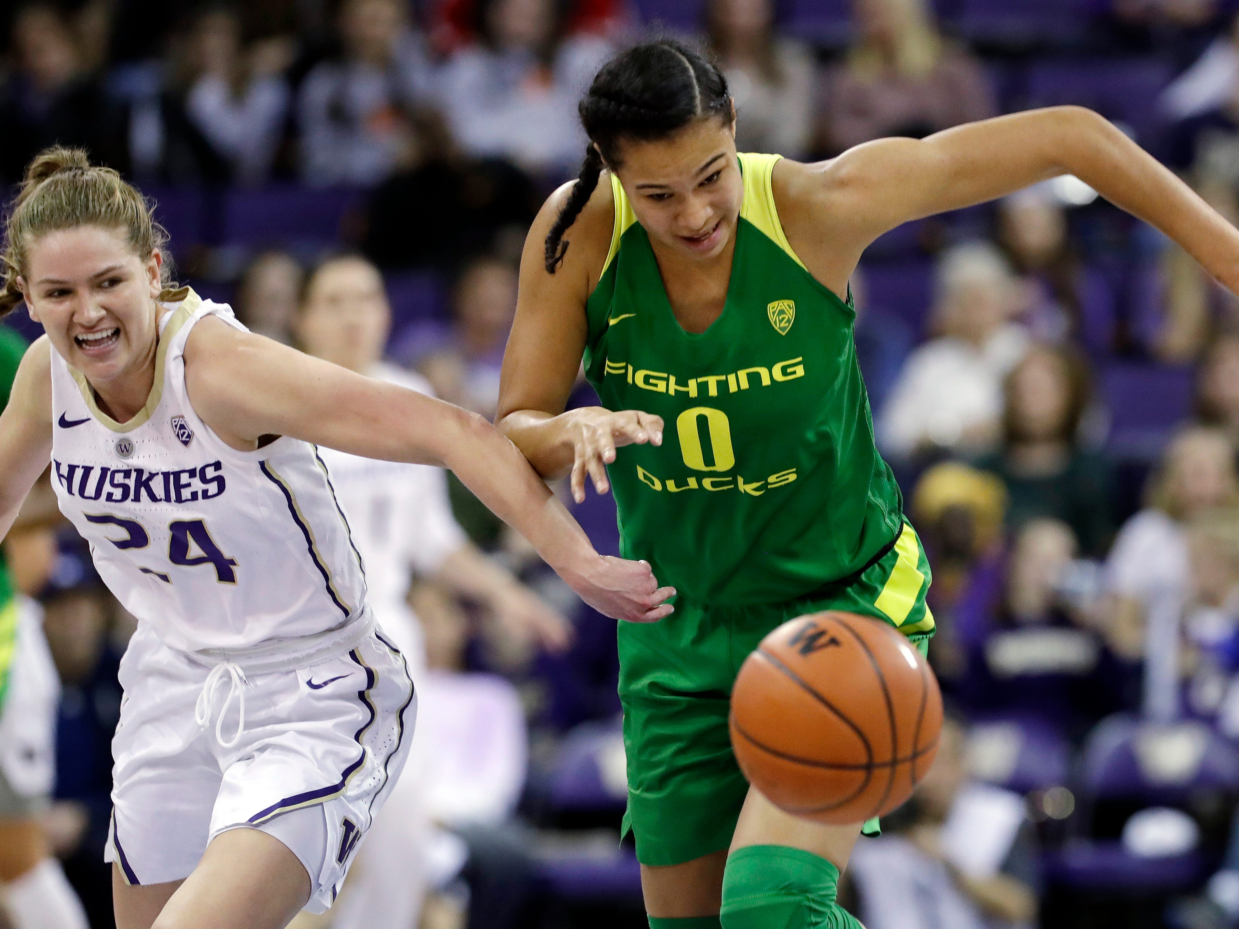 Oregon's Satou Sabally (0) races Washington's Jenna Moser (24) for a loose ball in the second half of an NCAA college basketball game Sunday, Jan. 27, 2019, in Seattle. Oregon won 76-57.