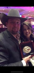 Josh Hilton and his wife Whitney Hilton pose with his Music Director of the Year award from the Professional Rodeo Cowboys Association. He won the award in 2017, which was the first time the PRCA offered it.