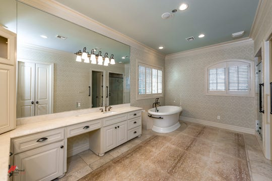 A luxurious master bath has marble counters, his/her vanities, soaking tub and a walk-in shower.