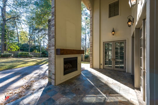 The outdoor living area has slate flooring and a fireplace and the open space allows for party spill-over.