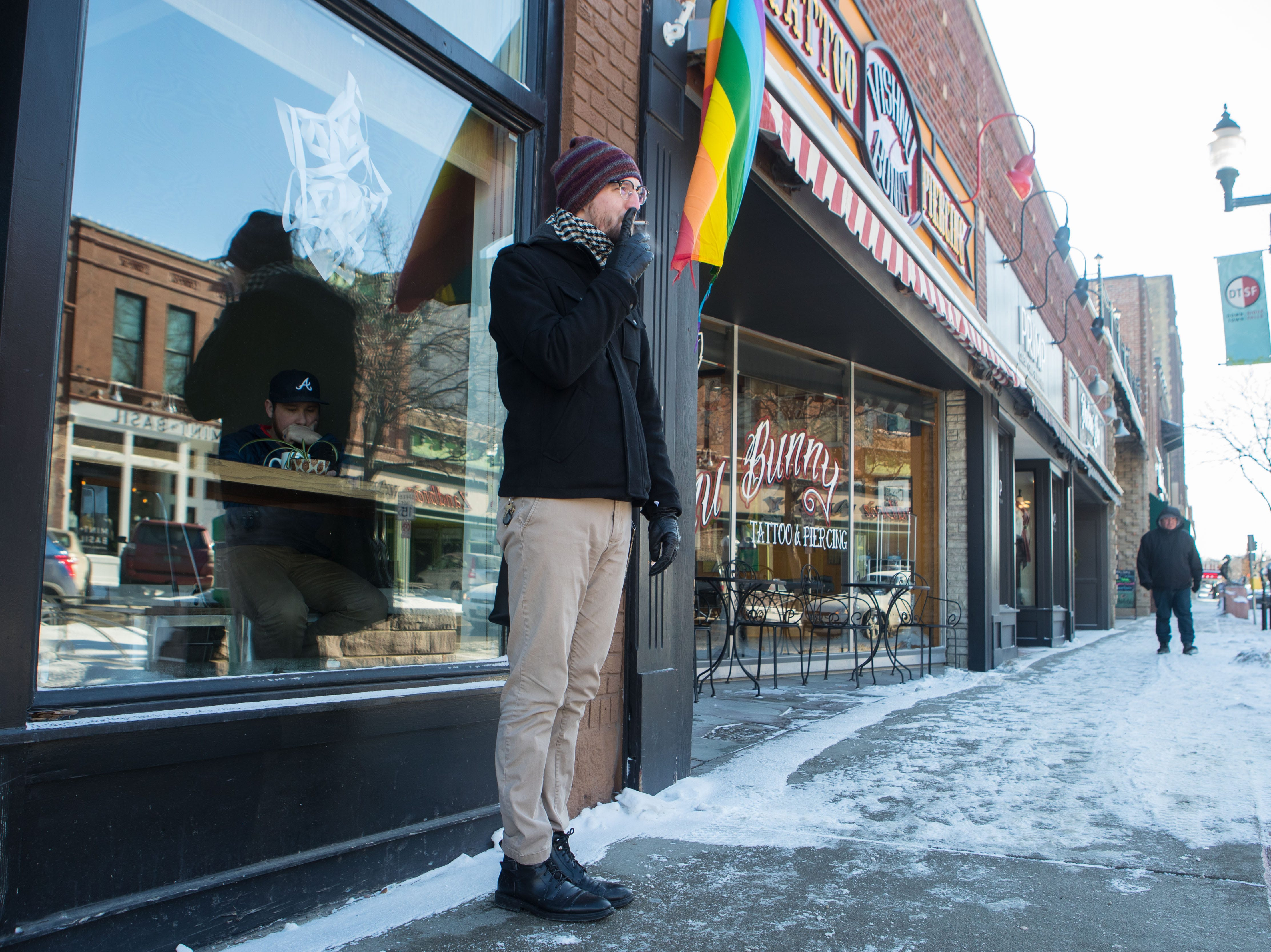 Austin Mielke takes a smoke break outside of Coffea in downtown Sioux Falls, S.D., Monday, Jan. 28, 2019.