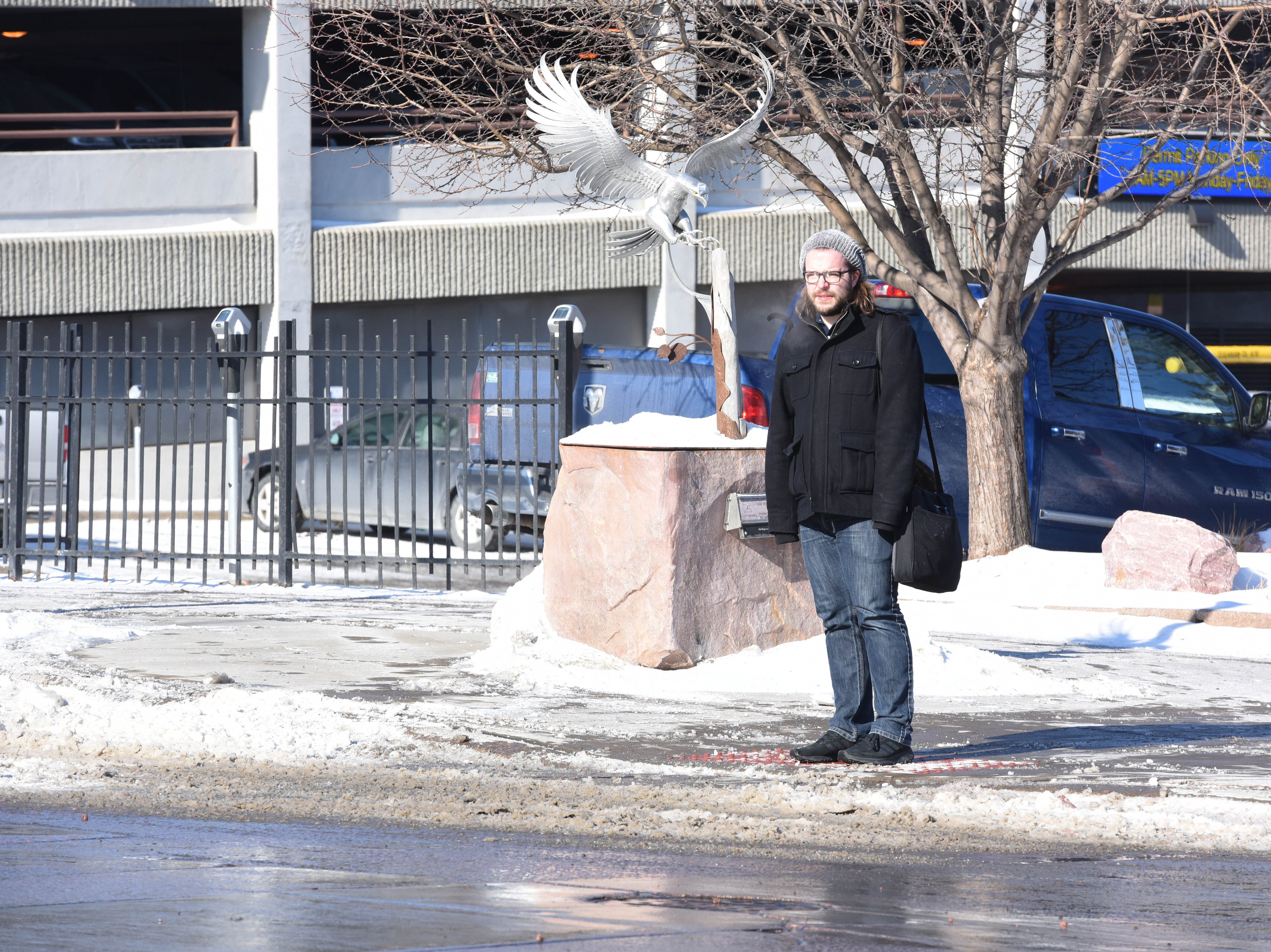 Luke Tatge waits at a cross walk in downtown Sioux Falls, S.D., Monday, Jan. 28, 2019.