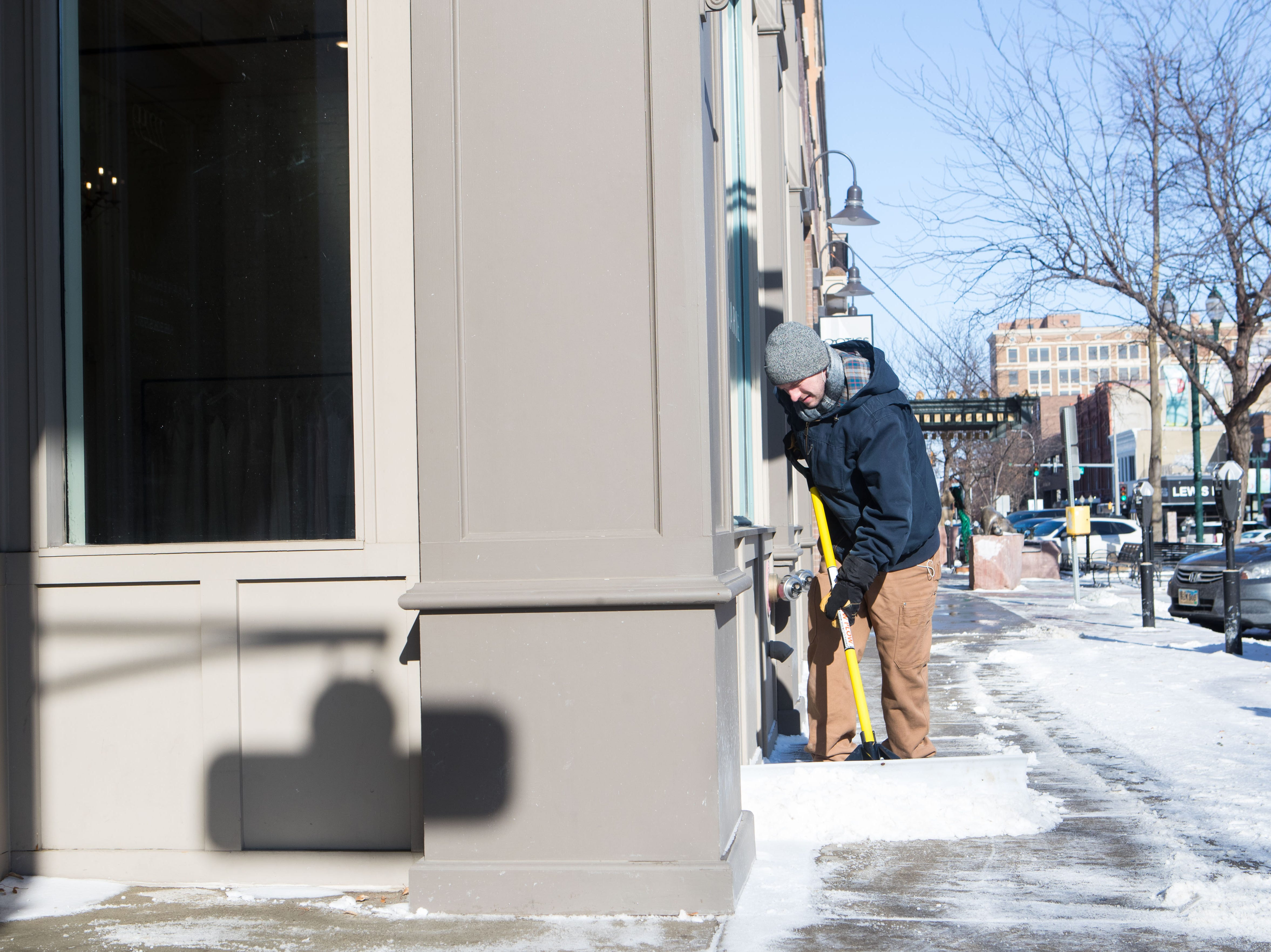 Jordan Hawks plows the sidewalk in downtown Sioux Falls, S.D., Monday, Jan. 28, 2019.