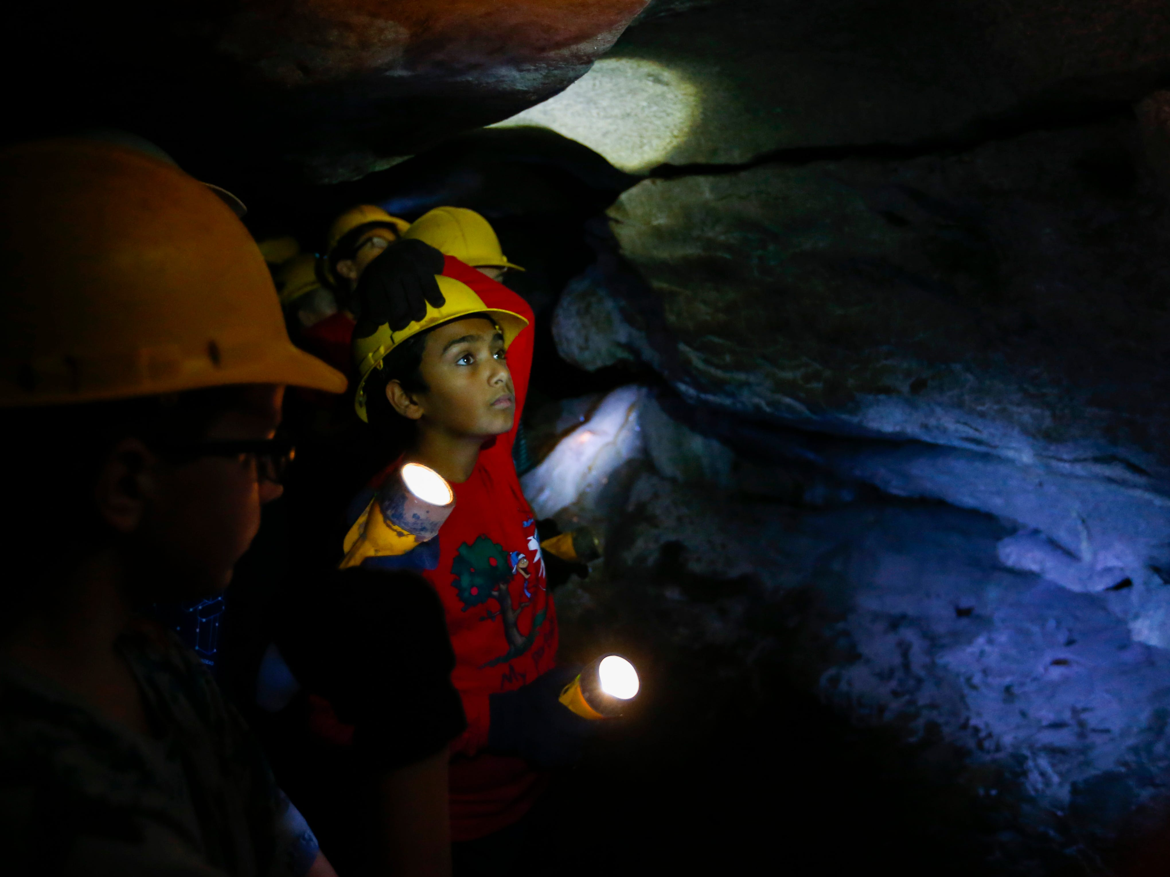 11-year-old Sanjeev Maganti looks at rock formations using a flashlight inside Giboney Cave in Doling Park on Wednesday, July 19, 2017. Middle school students took a tour of the cave during Springfield Public Schools' summer program, Explore.