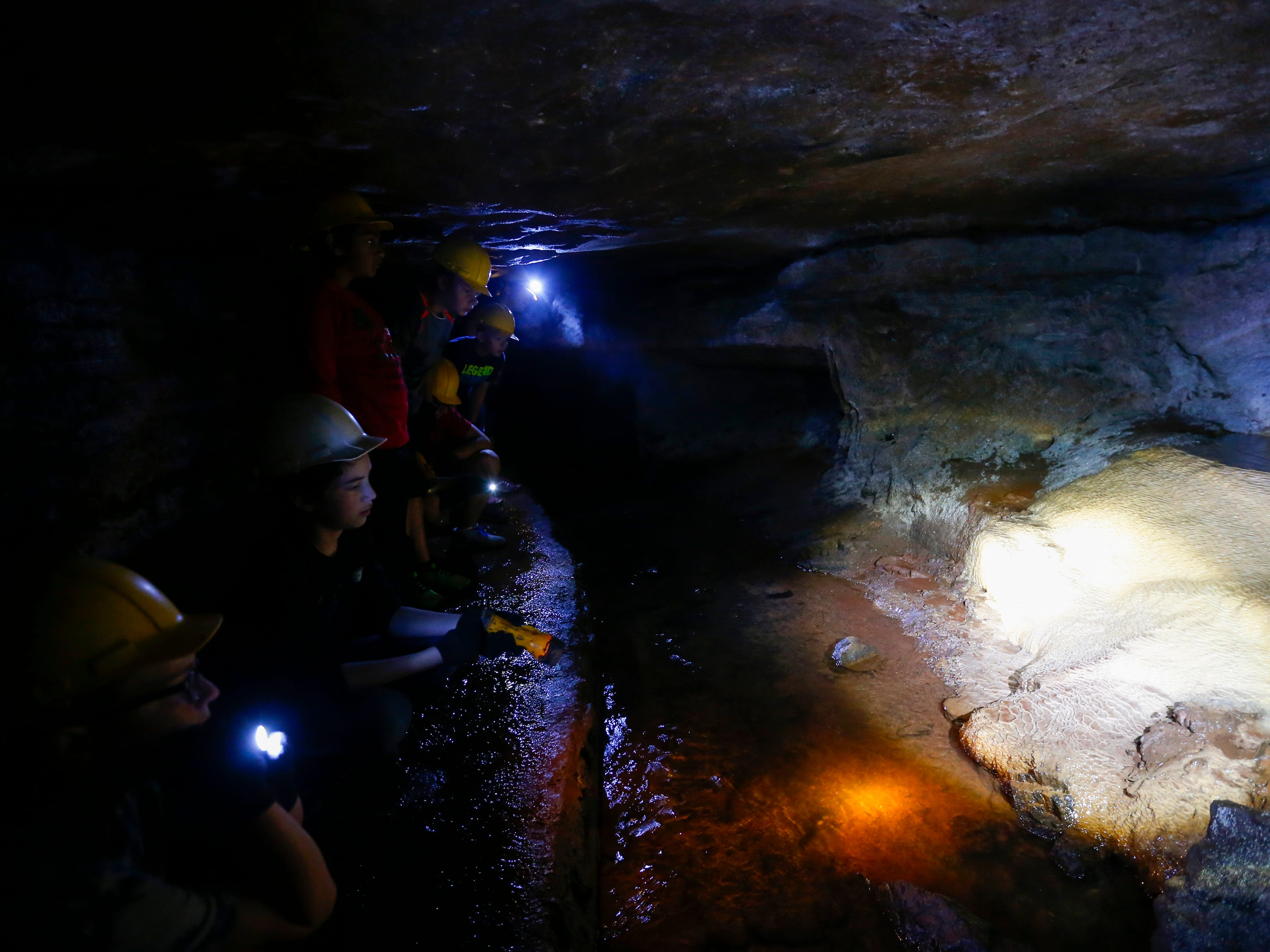 Using flashlights to illuminate their way, middle school students taking part in Springfield Public Schools' summer program, Explore, take a tour of Giboney Cave in Doling Park on Wednesday, July 19, 2017.