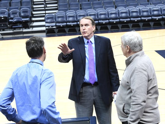 Dan Bonner talks with (left) UVA radio analyst Jimmy Miller and Wake Forest radio analyst  Mark Freidinger before the start of a men's basketball game Tuesday, Jan. 22 at John Paul Jones Arena.