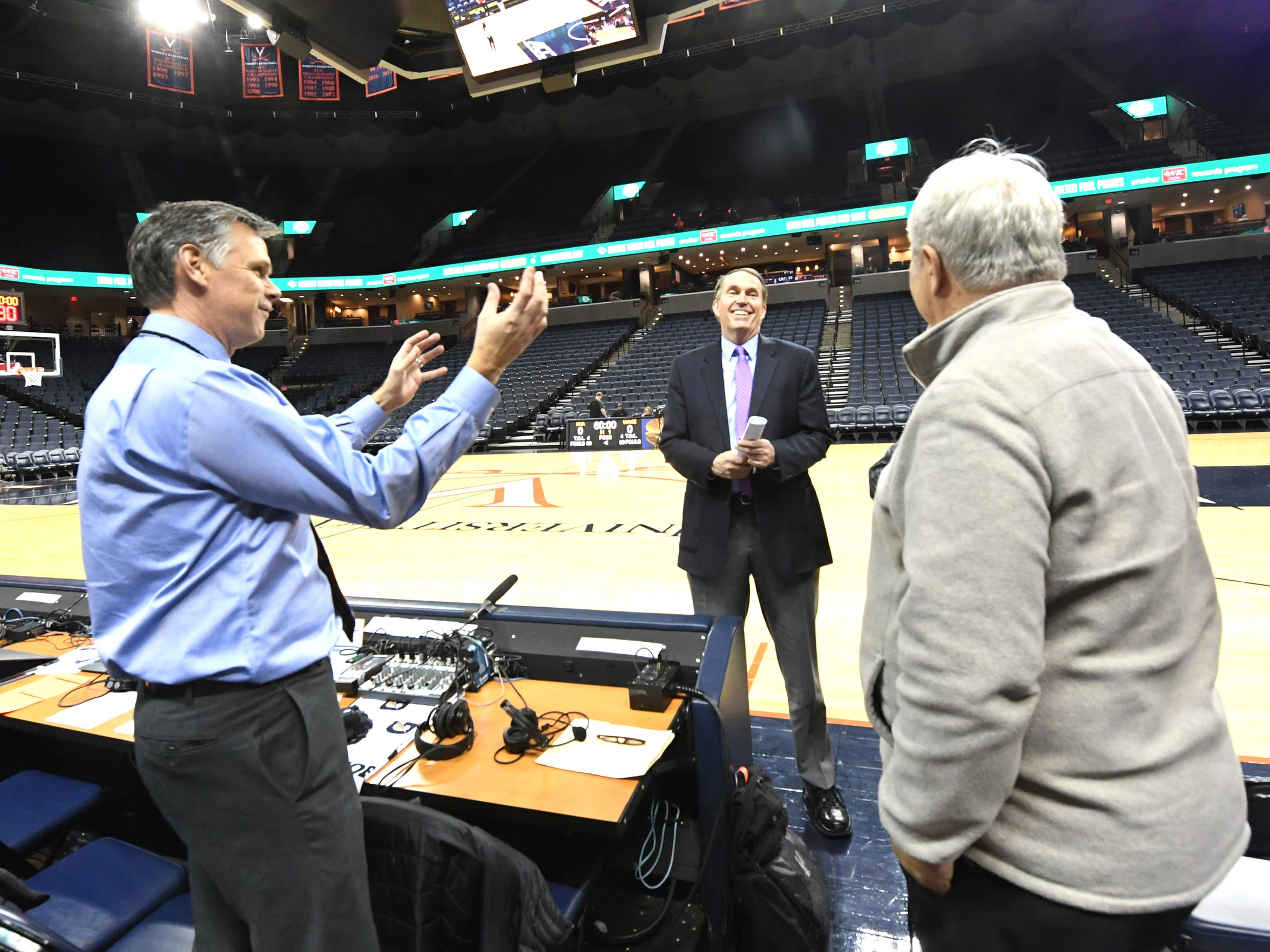 Dan Bonner talks with (left) UVA radio analyst Jimmy Miller and Wake Forest radio analyst  Mark Freidinger before the start of a men's basketball game Tuesday, Jan. 22 at John Paul Jones Arena.