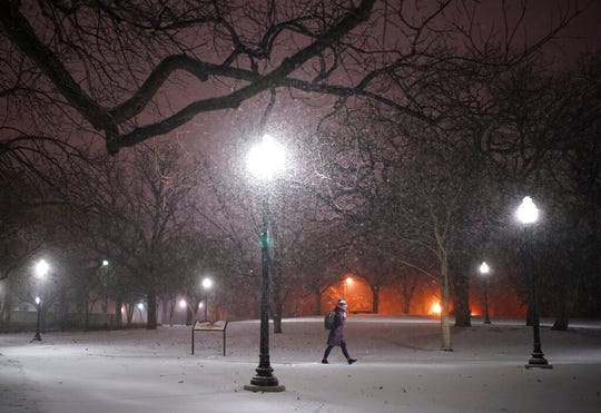 A woman walks across the snowy University of Minnesota campus near Dinkytown neighborhood in Minneapolis on Sunday, Jan. 27. A winter storm pushing across the Upper Midwest is expected to dump more than a foot of snow in parts of Minnesota and Wisconsin.