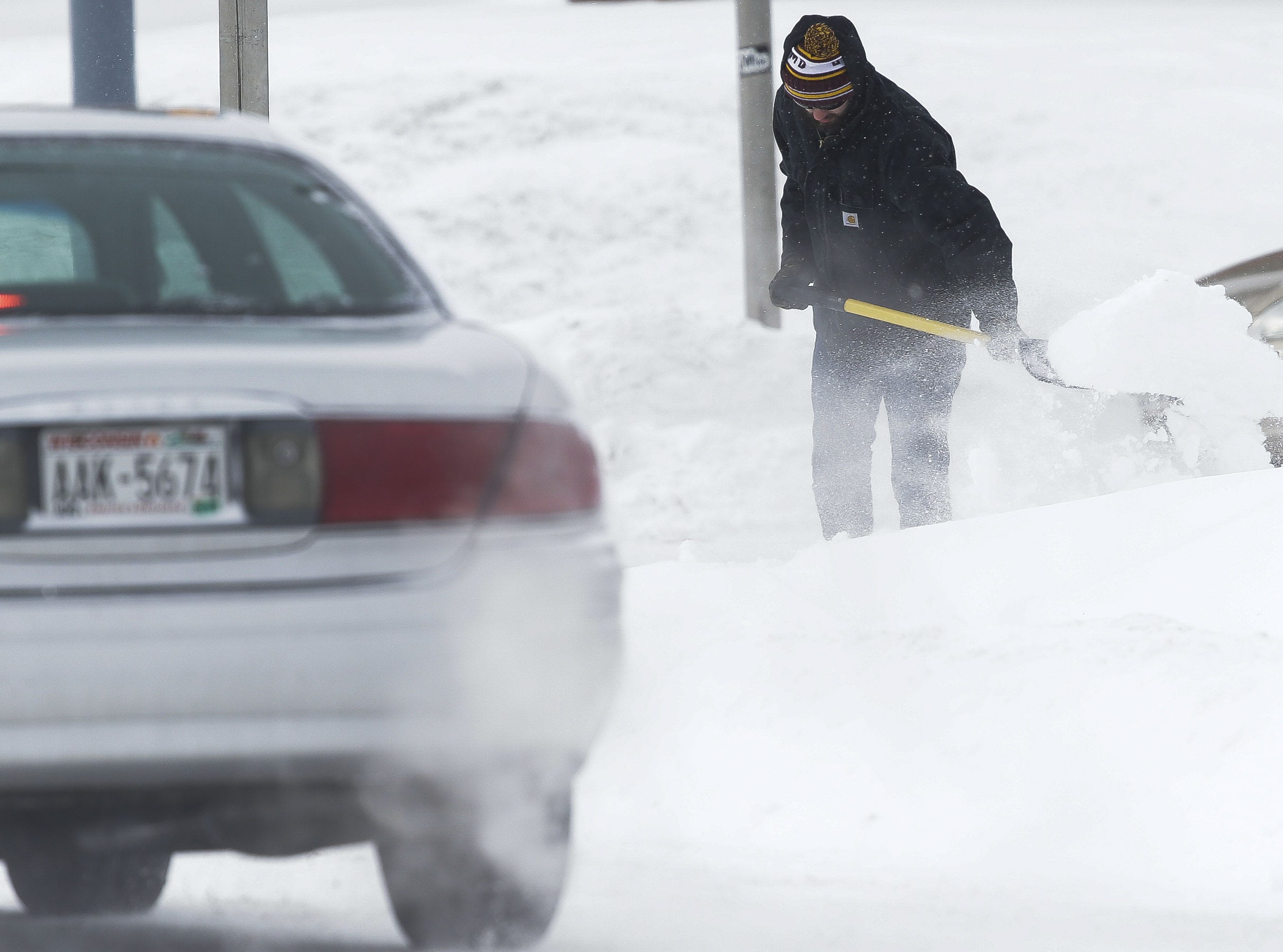Colin Filtz shovels snow on Monday, Jan. 28, 2019, on the UWSP campus in Stevens Point, Wis. A winter storm rolled through Wisconsin on Sunday and Monday, marking the first major snowfall of the season.