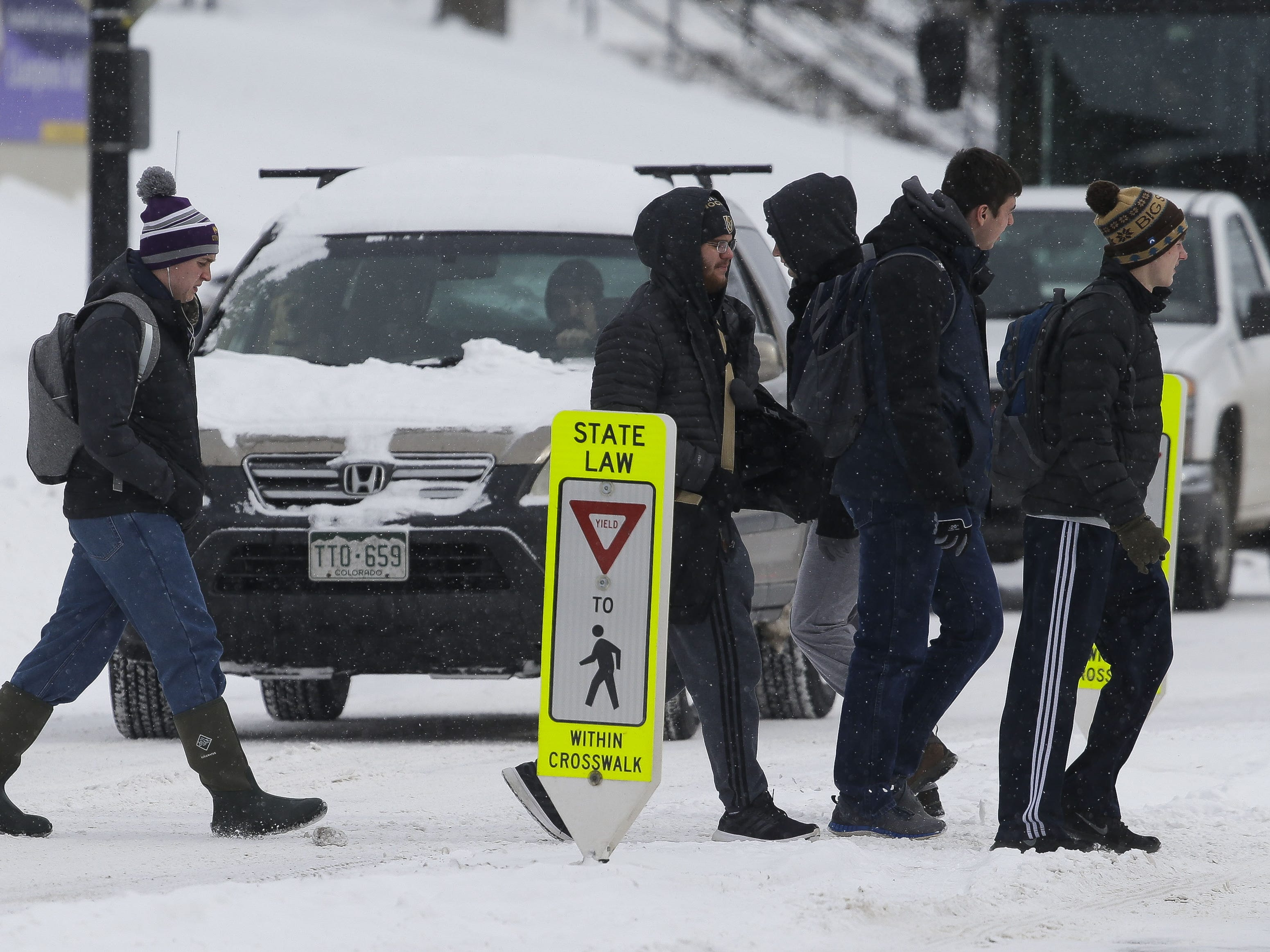 UWSP students cross the street on Monday, Jan. 28, 2019, in Stevens Point, Wis. A winter storm rolled through Wisconsin on Sunday and Monday, marking the first major snowfall of the season.