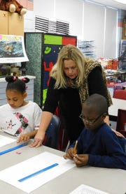 Heather Mott assists a student in brainstorming ways to visually depict his emotions.