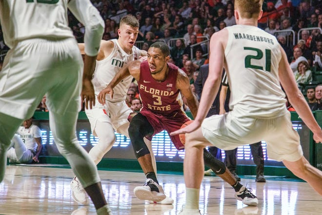 Florida State guard Trent Forrest (3) drives past Miami players during the second half of a basketball game at the Watsco Center in Coral Gables, FL, on Sunday, January 27, 2018.