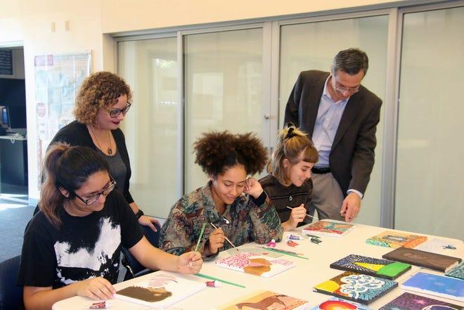 Instructor Alexandria Gribble and artist Rob Otteson look over kinetic pointillism work created by students Crystal Aguilar, Mya DeSimone and Sophia Demiduke.