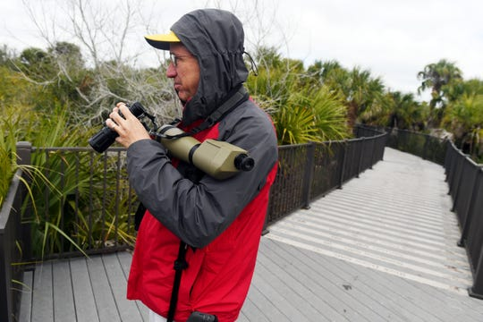Bill Rogers, of Oak Ridge, Tennessee, scans the waterways for birds on the Centennial Trail on Monday, Jan. 28, 2019 at Pelican Island National Wildlife Refuge in Indian River County. Monday marked the first day that refuge staff returned to work after the 35-day federal government shutdown.