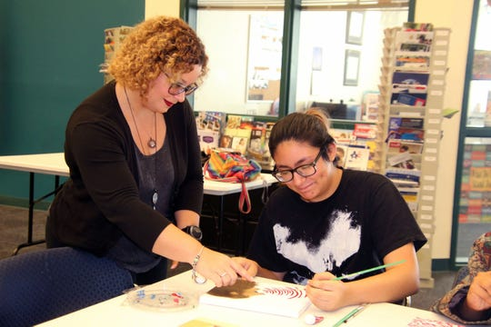 Instructor Alexandria Gribble works with student Crystal Aguilar on kinetic pointillism.