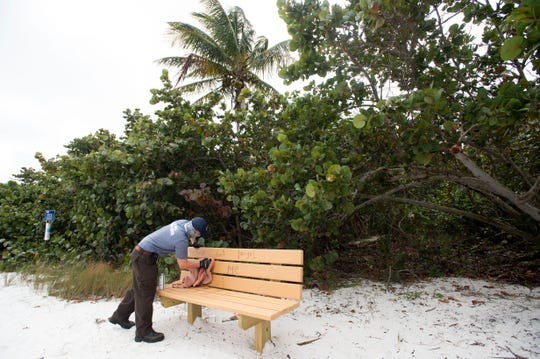 Jeremy Carr, a full-time volunteer with the Hobe Sound National Wildlife Refuge, cleans a bench that was damaged by graffiti during the 35-day government shutdown on the first day back to work for federal workers Monday, Jan. 28, 2019, at the Hobe Sound Nature Center in Hobe Sound.