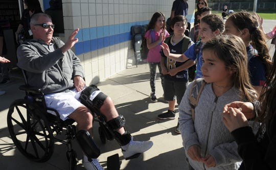Bob Belanger,  a Simi Valley crossing guard who was hit and seriously injured by a vehicle that ran a red light last October near Madera School in Simi Valley, waves to students Friday during a ceremony at the school. Belanger, known to students as Mr. Bob pushed a woman he was helping cross the street to safety before he was hit. He is still recovering from his injuries and has another surgery scheduled this week on his leg.