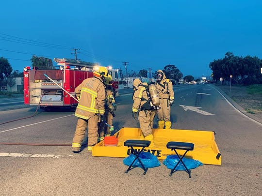 Firefighters don gear to deal with potentially hazardous material Sunday morning near Oxnard and Statham boulevards.