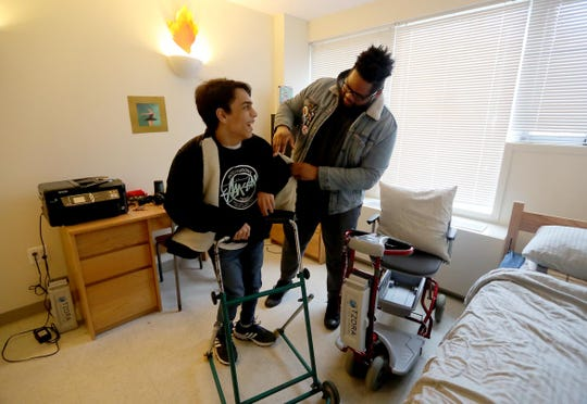 Nick Astor, a freshman at Purchase College, puts on his coat Jan. 25, 2019 with the help of his live in aide, Kashif Wright, who lives in the room next door. Along with Kashif, Nick, who has cerebral palsy, has several student aides that also help provide almost round the clock care. A change in Gov. Cuomo's budget may now make it more difficult for Nick to continue to get the care that he needs  in order to be able to live on campus while attending college.