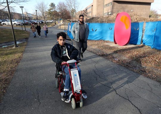Nick Astor, a freshman at Purchase College, uses his motorized scooter to get around campus Jan. 25, 2019. Walking with him is his live in aide, Kashif Wright, who lives in the room next door. Along with Kashif, Nick, who has cerebral palsy, has several student aides that also help provide almost round the clock care. A change in Gov. Cuomo's budget may now make it more difficult for Nick to continue to get the care that he needs  in order to be able to live on campus while attending college.