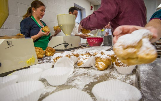 In this file photo, parents, alumni and friends of Mount Aviat Academy work together to produce 5,200 cream puffs.