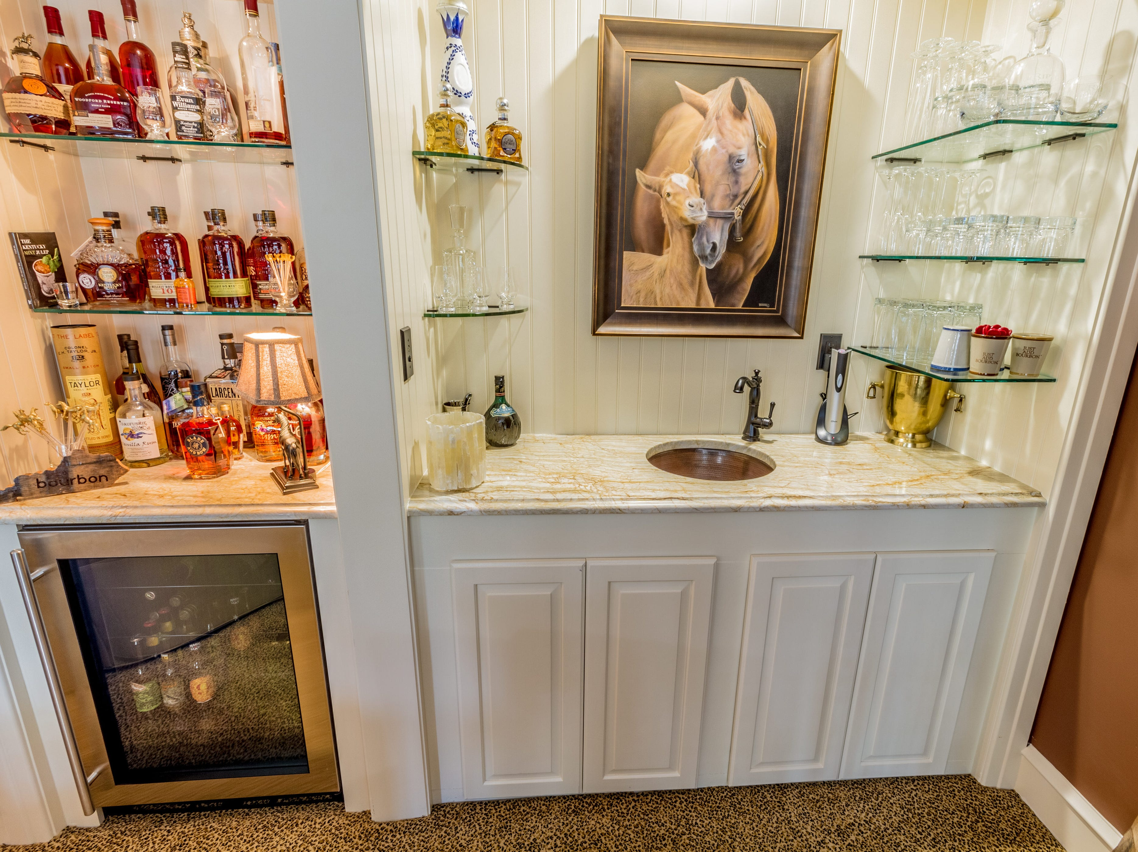 The second-floor family room at 1100 N. Rodney St. has a fireplace, bar and wine fridge and is decorated in a bourbon theme.