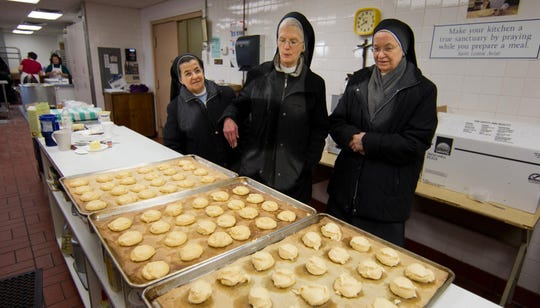 In this file photo, Sister Anne Elizabeth (center) gives a tour of the cream puff sal to visiting sisters Ana Elizabeth from a parish in Columbia, South America, (left) and Rose Agnes, who is Swiss-German. Mount Aviat Academy in Childs, Maryland, has an annual cream puff sale to raise money for the Oblate Sisters of Saint Francis de Sales.