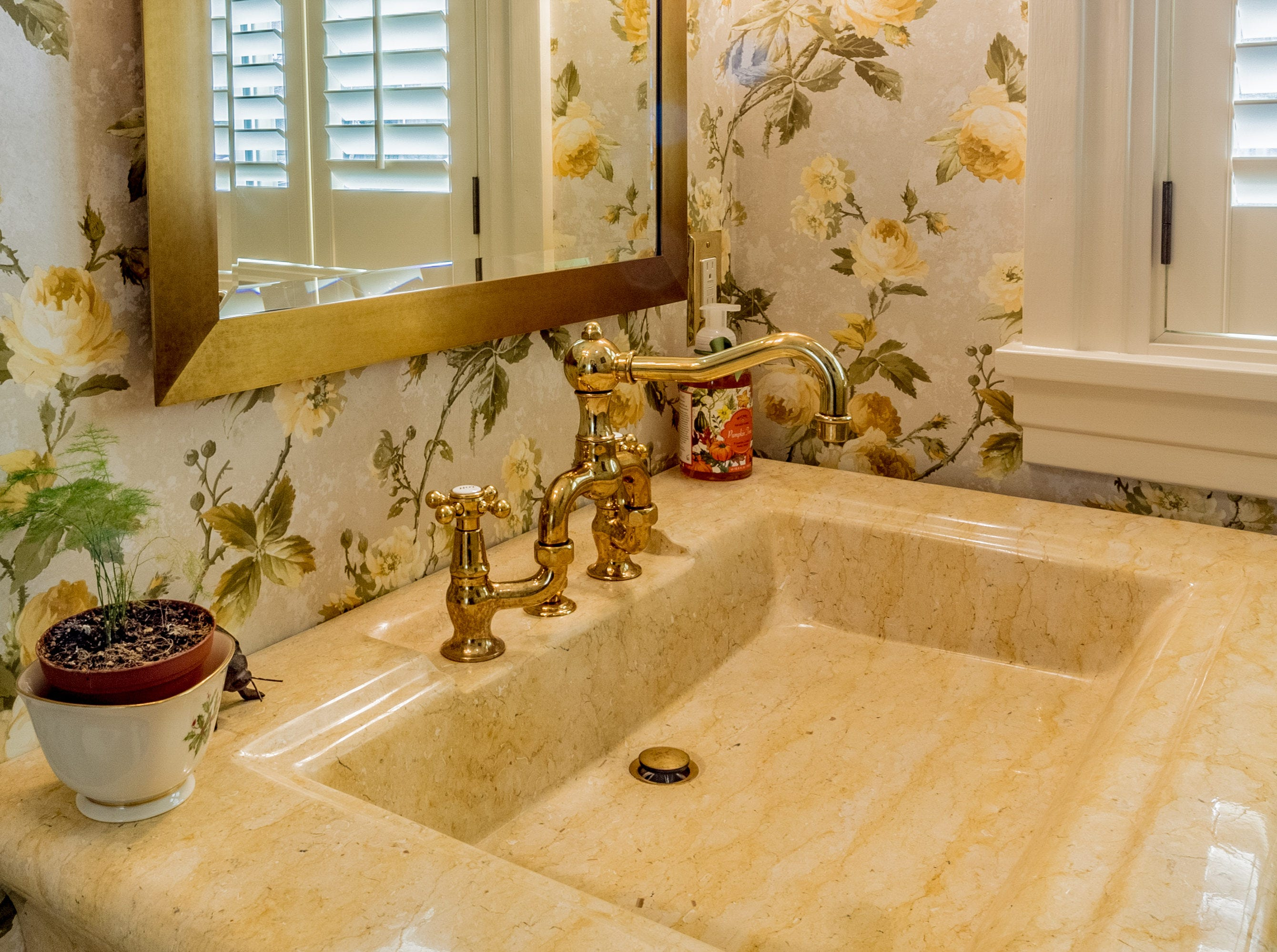 A pedestal sink with a gold faucet is one of the details that makes the powder room shine.