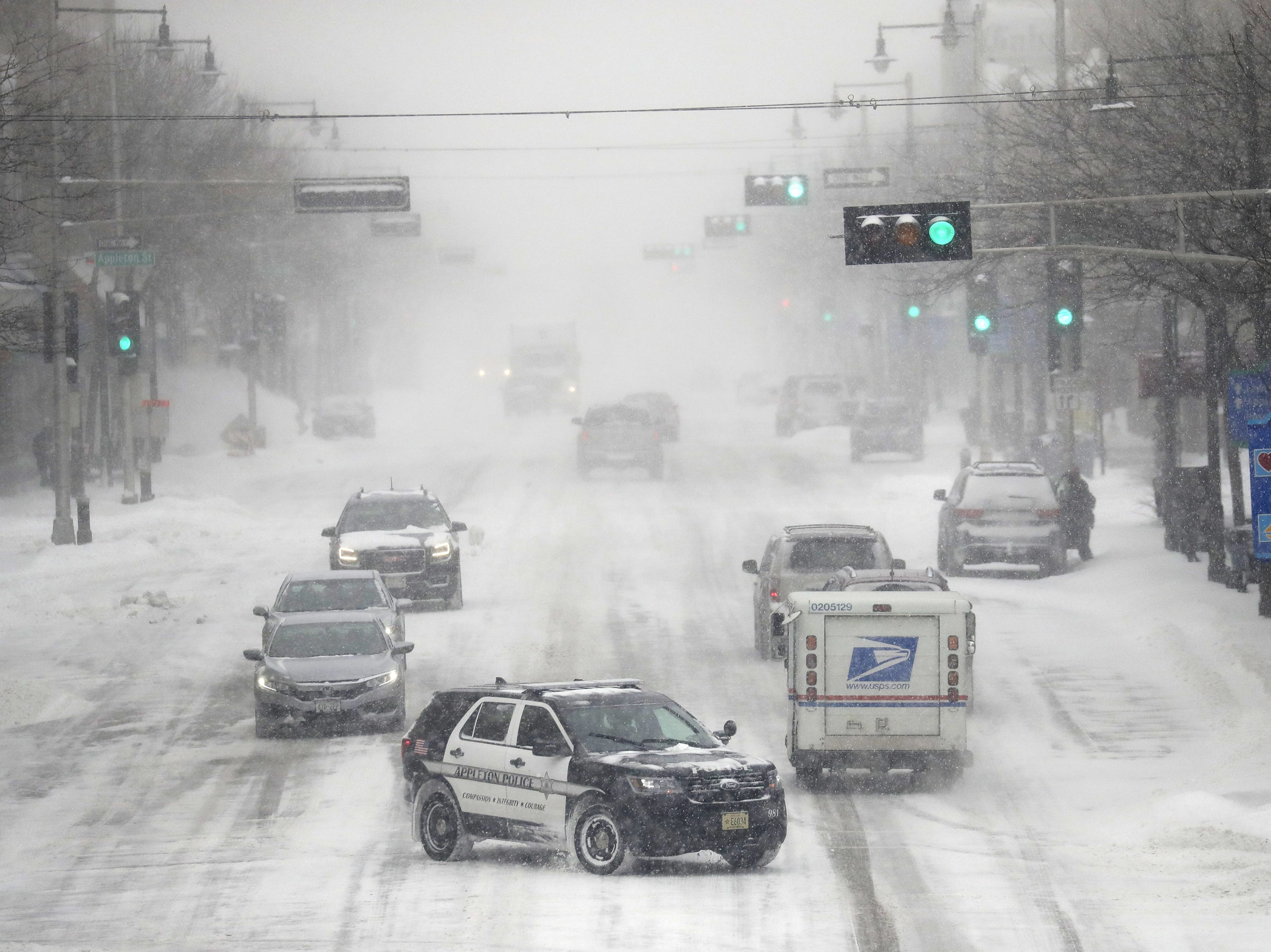 Traffic moves slowly along College Avenue during a snowstorm Monday, Jan. 28, 2019, in downtown Appleton, Wis.