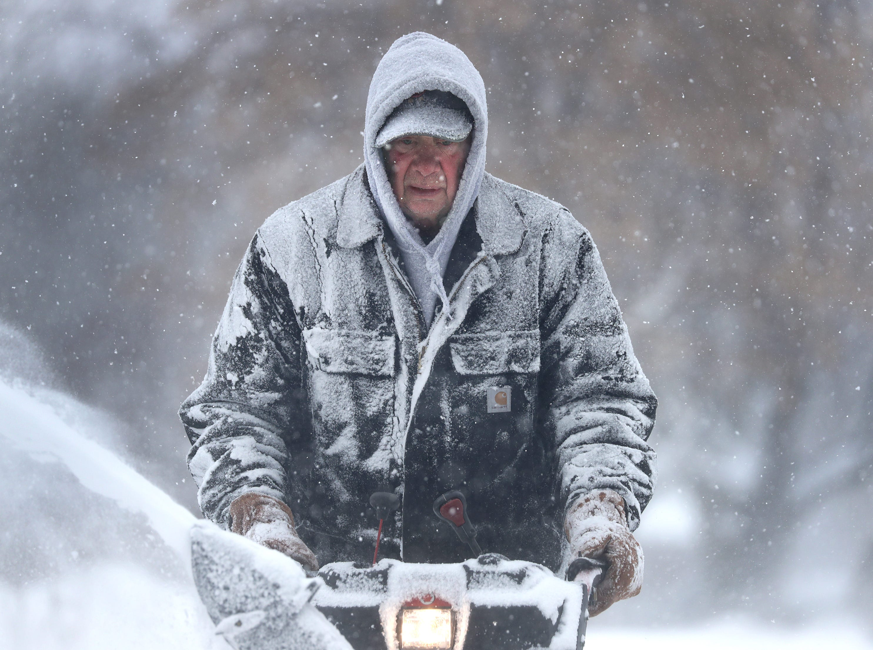 Gary Verstegen clears a sidewalk as a winter storm moves through Wisconsin on Monday, Jan. 28, 2019, in Little Chute, Wis.