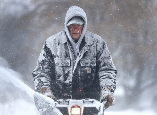 Gary Verstegen clears a sidewalk as a winter storm moves through Wisconsin on Monday, Jan. 28, 2019, in Little Chute, Wis.